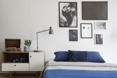 Skandinavische stijl, houten opmaker door een marineblauw bed en ontworpen kunstgalerie op een witte muur van een creatieve slaap stock afbeeldingen