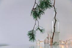 Skandinavischer Weihnachtsdekor Kiefernniederlassungen, Girlande und eine keramische Hauslampe stockfotos
