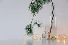Skandinavischer Weihnachtsdekor Kiefernniederlassungen, Girlande und eine keramische Hauslampe stockbild