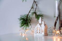 Skandinavischer Weihnachtsdekor Kiefernniederlassungen, Girlande und eine keramische Hauslampe stockfoto