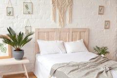Skandinavisches angeredetes Schlafzimmer mit Makramee auf der Wand lizenzfreies stockfoto