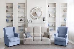 Skandinavisches Artwohnzimmer mit der beige Couch mit den Kissen und zwei blauen Lehnsesseln morgens hell lizenzfreie stockfotografie