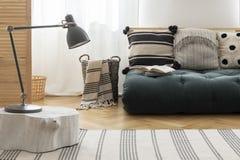 Skandinavisk futon med mönstrade kuddar på den vita väggen och parketten på golvet, verkligt foto royaltyfri bild