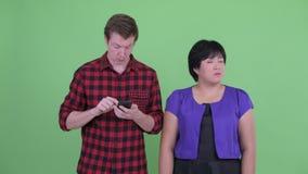 Skandinavisk hipsterman som använder telefonen och överviktigt asiatiskt vänta för kvinna arkivfilmer