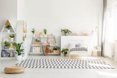 Skandinavisk stil, trämöblemang med växter och berggarneringar i en solig monochromatic barnsovruminre med wh royaltyfri fotografi