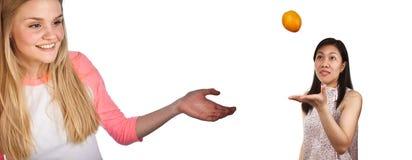 Skandynawska śliczna młoda dziewczyna z ręką pokazuje azjatykciego dziewczyny jugg zdjęcie stock