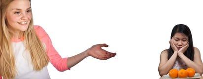 Skandynawska śliczna młoda dziewczyna z ręką pokazuje zanudzającej azjatykciej dziewczyny zdjęcie royalty free