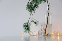 Skandynawski Bożenarodzeniowy wystrój sosen gałąź, girlanda i ceramiczna domowa lampa, obraz stock
