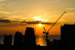 Skapa byggnader med havet på solnedgångljus arkivbild