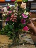 Skapa en blom- bukett med blandade rosa färger på blomsterhandeln Blomsterhandlarehänder som arbetar olik etnicitet fotografering för bildbyråer