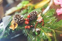 Skapa en julkrans som göras av granfilialer, sörjer dekorativa bär, kottar och dekorativa leksaker i arbetsplatsen Royaltyfri Foto