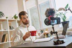 Skapa innehållet Gladlynt manlig blogger som gör en ny video för hans vlog och dricker ett te, medan sitta inomhus royaltyfri fotografi