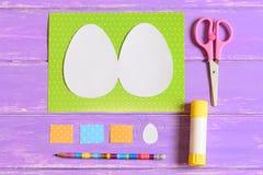 Skapa kortet för hälsning för påskägg moment handbok Kulört papper täcker, mallar i form av ägget, sax, limpinnen, blyertspenna Arkivfoton