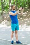 Skapa ruttkörningen genom att använda applikation Mansmartphonen som är klar att starta, joggar Aktiveringsapplikation Idrottsman royaltyfria foton