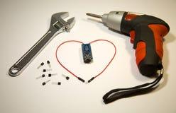 Skapad hjärta av trådar och transistorer, stående nästa drillborr och skiftnyckel arkivbilder