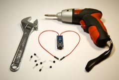 Skapad hjärta av trådar och transistorer, stående nästa drillborr och skiftnyckel royaltyfri fotografi