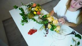 Skapar märkes- färger för ung gullig kvinna från specialtillverkade tematiska sammansättningar för blommor, på tabellen i regerin lager videofilmer