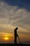 Skarbu myśliwy z wykrywaczem metalu na zmierzchu na plaży z planem w niebie Fotografia Stock
