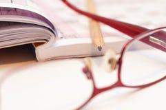 Skarp blyertspenna i fokus, monokel och korsord royaltyfria bilder