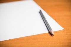 Skarp blyertspenna och tomt ark av papper Fotografering för Bildbyråer