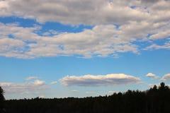 Skarp sikt av klara himlar och fluffiga moln arkivfoto