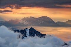 Skarpa kanter ovanför havet av moln som är upplysta av den stigande röda solen Arkivfoton