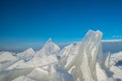 Skarpa stycken av is mot blå himmel Arkivfoto
