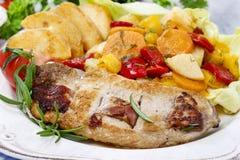 Skarv av griskött med bakade potatisar och nya grönsaker royaltyfri foto