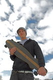 Skate boarder. Young man holding a long board, with clouds and blue sky background Stock Photo