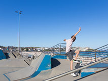 Skate boarder performs tricks, Sydney. Sydney - March 1, 2016: skate boarder performs tricks in Sate Park with interesting slides in the beautiful city beach and Royalty Free Stock Images