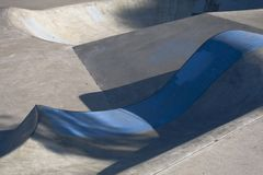 Skate Bowl with Blue Lip. A skateboard park bowl with a blue painted concrete lip Royalty Free Stock Photos