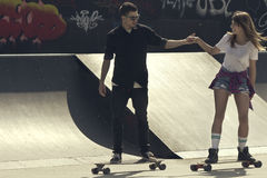 Skate couple. Two young people skateboarding in skate park royalty free stock images