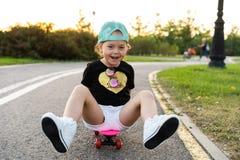 Skate da equitação da criança no parque do verão Menina que aprende montar a placa do patim Esporte exterior ativo para a escola  foto de stock royalty free