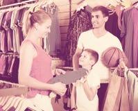 Skate de compra do homem e da mulher para o filho na loja do esporte Imagem de Stock Royalty Free