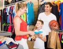 Skate de compra do homem e da mulher para o filho na loja do esporte Fotos de Stock Royalty Free