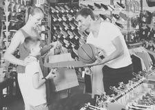 Skate de compra do homem e da mulher para o filho na loja do esporte Fotografia de Stock Royalty Free