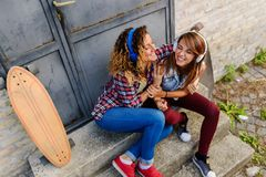 Smiling skateboarding girls sitting in the street hanging out listening music stock photos
