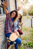 Smiling skateboarding girls sitting in the street hanging out Royalty Free Stock Photos