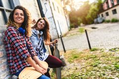 Smiling skateboarding girls sitting in the street hanging out Stock Photos
