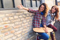 Smiling skateboarding girls sitting in the street hanging out Royalty Free Stock Photo