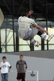 Skate jump 1. A skater is jumping high while other guys in the background are watching him Stock Image