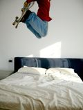 Skate jump over bed. Skate jump over an unmaked double bed, white background Royalty Free Stock Photos