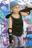 Skate kid. A boy with skateboard by a grungy colourful wall Royalty Free Stock Photos