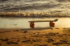 Skate na areia na praia no por do sol imagem de stock