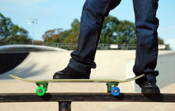 Skate Park America. A skater balances on the rail at the skate park. The ramps and stunt areas of the park are in the background Royalty Free Stock Images