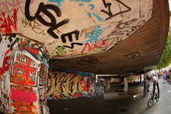 Skate park graffiti. Black teenager riding BMX at the graffiti covered skate park on the South Bank in London Stock Images
