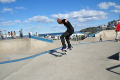 At the skate park near Sydney, Bondi Beach with the man in black jean and tee shirt showing his professional skateboard skill. royalty free stock photos