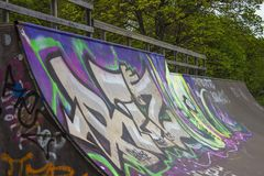 Skate ramp covered in Graffiti Art with trees in background. Skate ramp covered in Graffiti Art Royalty Free Stock Image
