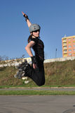 Skate roller jump. Women skate roller jump with one hand up. In black clothes, sun glasses and gray helmet Royalty Free Stock Image