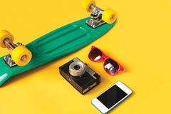 Skate verde, óculos de sol vermelhos, câmera do vintage e smartphone da tela em um fundo amarelo Foto de Stock